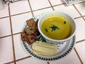 Soup, crackers and cheese slices arranged on a plate