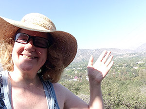 Laurie waves from the top of a trail at Descanso Gardens