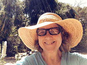 Laurie in front of the white flower bed at Descanso Gardens on a sunny day