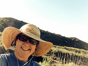 Laurie smiling in her straw hat on a sunny day on the trail in the foothills.