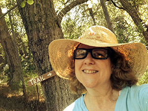 Laurie in a straw sunhat by a tree marked with a trail sign.
