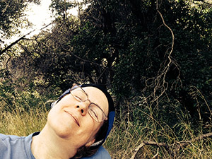 Laurie rests with her eyes shut under the tree at the trail head