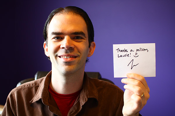 """Josh Woodward holds a sign saying """"Thanks a Million Laurie!"""""""