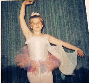 Laurie at age 7 wearing a rainbow colored tutu