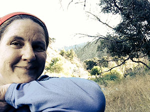 Laurie leaning her chin on her arm up in a grove on the hiking trail.