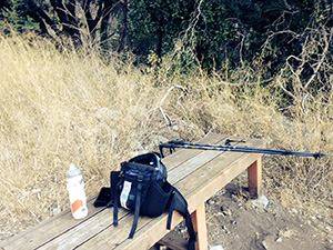 A bench with Laurie's pack, water bottle and hiking poles laid on it.