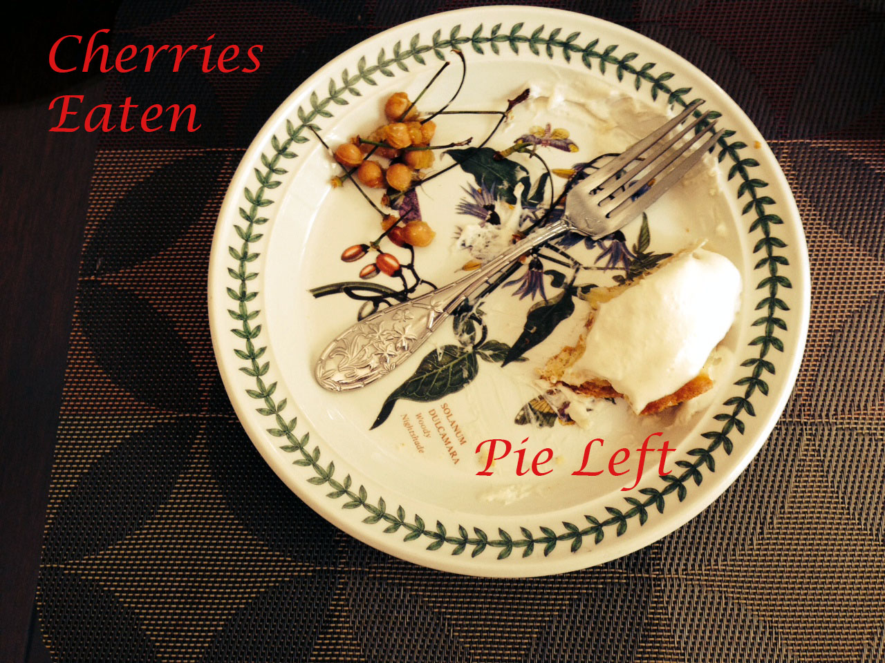 Plate with cherry pits and part of a pie slice