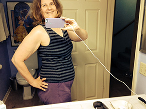 Laurie sideways in her bathroom mirror, hand on hip, wearing tank top and shorts