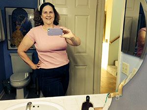 Laurie in a pink T-shirt and jeans viewed in a mirror.