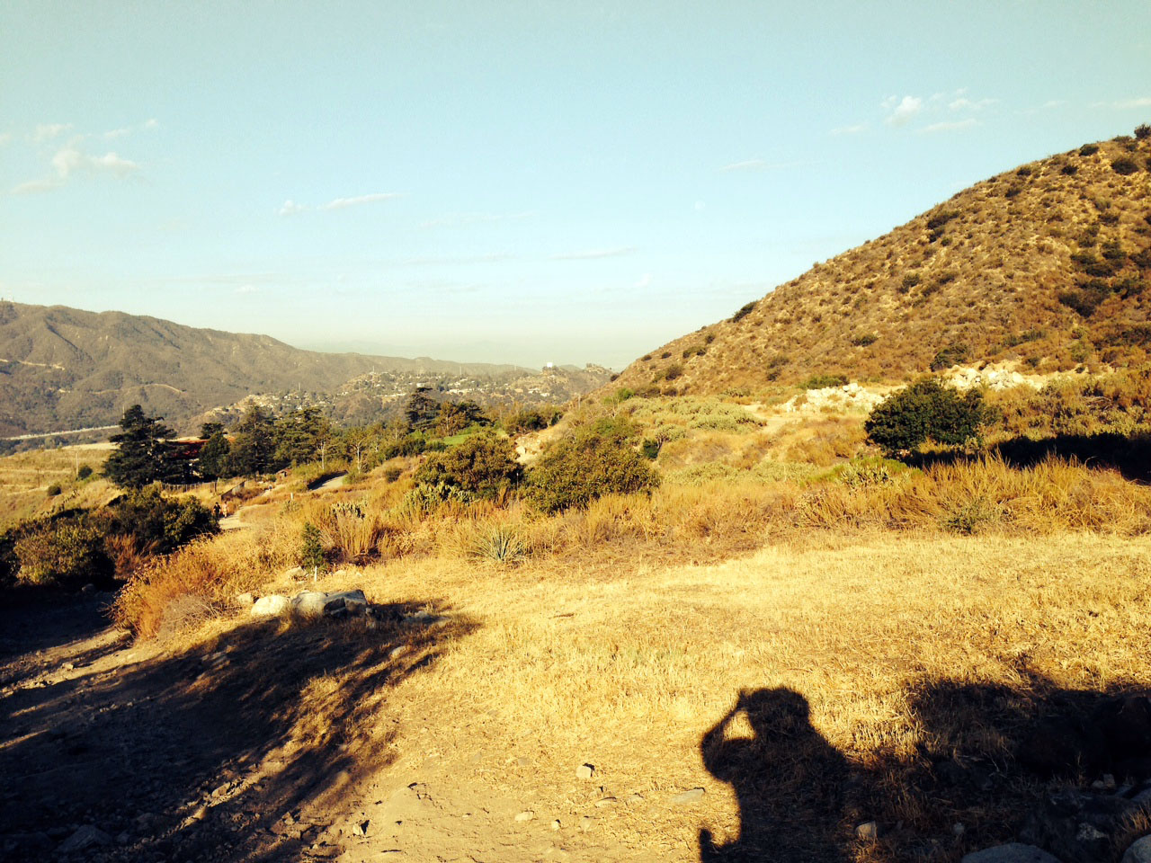 Laurie's shadow as she snaps the photo against the brown grass of the foothills on the hiking trail.