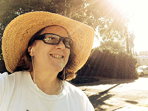 Laurie smiling in her straw hat with the sun shining down.