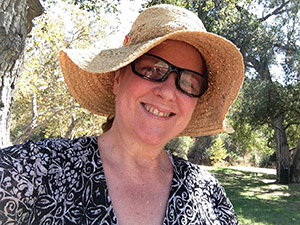 Laurie in a black print blouse and straw hat