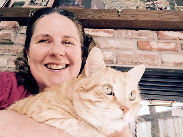 Tiger the cat in Laurie's arms in front of the fireplace