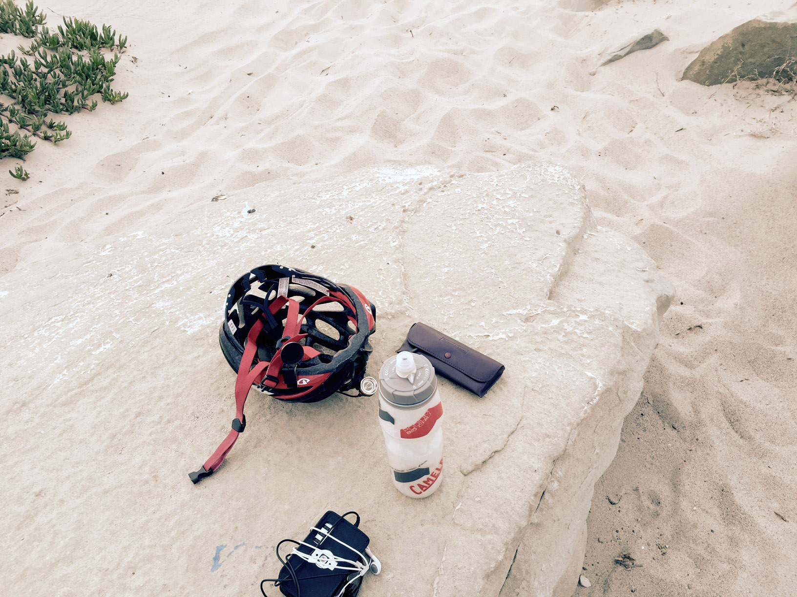 Laurie's bike helmut and podcast gear on a large sandy colored flat boulder on the beach