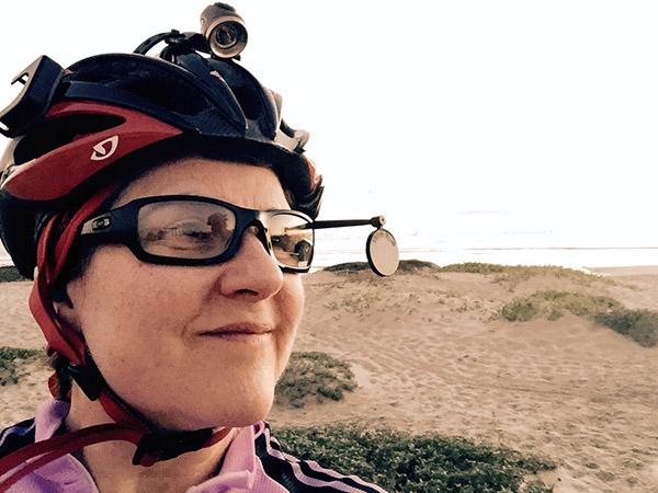 Laurie looking back via bike helmet mirror near the beach