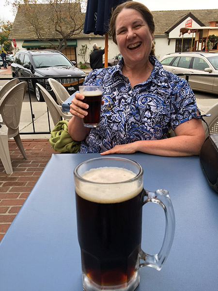Laurie seated across a table raises a small beer with a huge glass of beer in the foreground