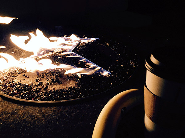 Close up of the lit fire pit in the darkness. Coffee cup and banana in silhouette on its edge.