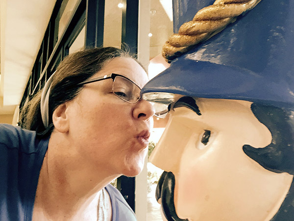 Laurie puckering up to kiss a large wooden nutcracker's nose