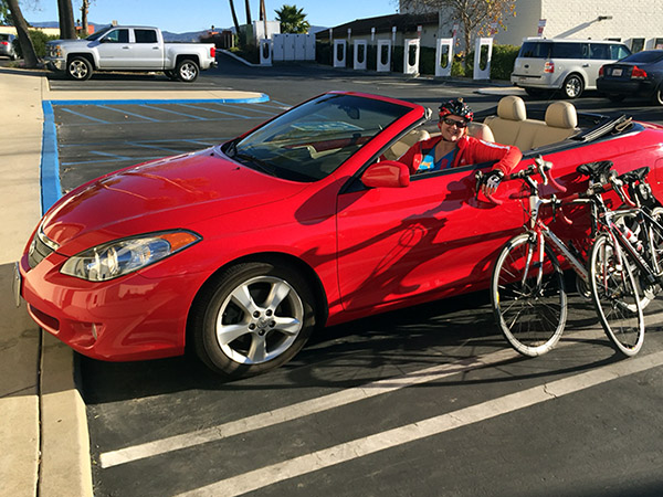 Laurie in a red convertible with bikes leaned against it