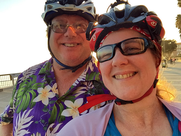 Laurie and Mark in bike gear - head shots - sun is beginning to sink - on the boardwalk by the Pacific Ocean in Ventura