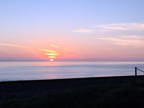 Glowing orange-pink sun sinks into the purple ocean