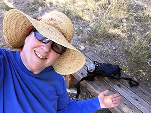 Laurie in her straw hat taken from overhead pointing out a wooden bench