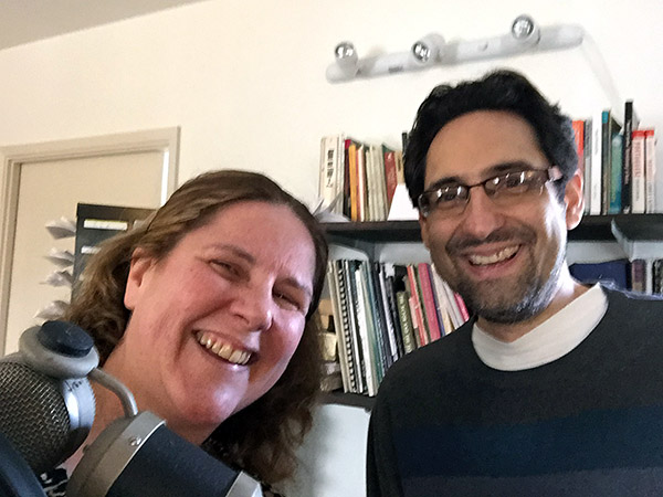Laurie and David Babich in his studio by a mic in front of his bookshelves