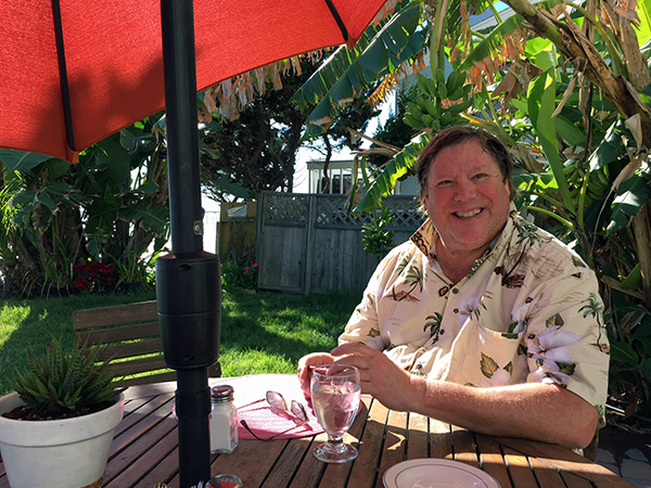 Mark at an outside table with red market umbrella. He's smiling and wearing a Hawaiian shirt