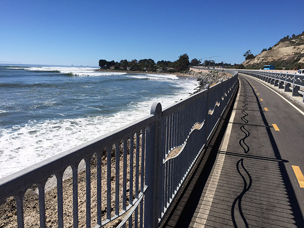 A decorative railing separates the bike path from the beach and the traffic.