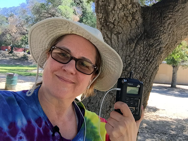Laurie in a rainbow tie-dye jacket and hiking hat standing under a tree with her recorder.