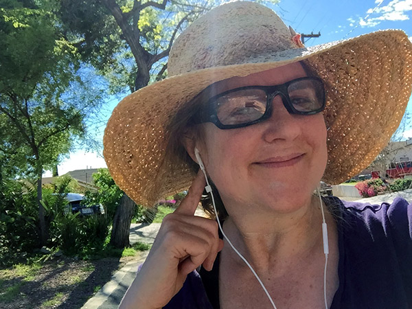 Laurie in a sun hat walking through her neighborhood. She's pointing to her earbuds.
