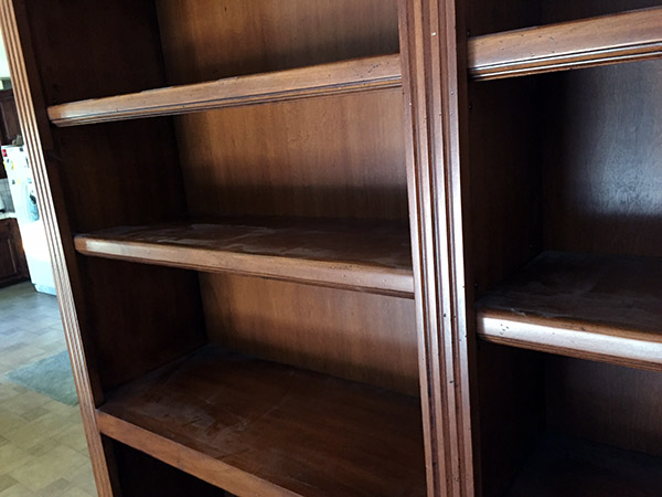 Dusty empty bookcase shelves showing marks where items had been sitting.