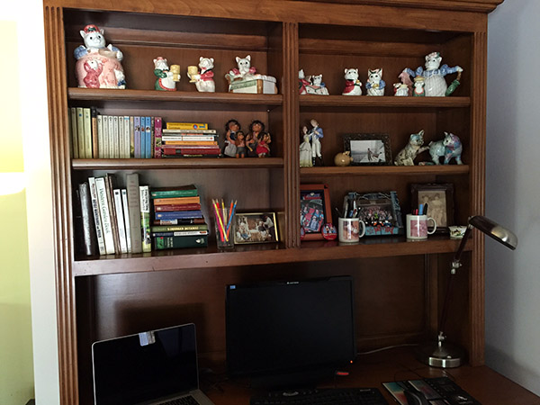 Clean and organized computer hutch with well spaced china figurines and books. Not crowded.