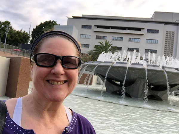 Laurie in front of a large outdoor fountain