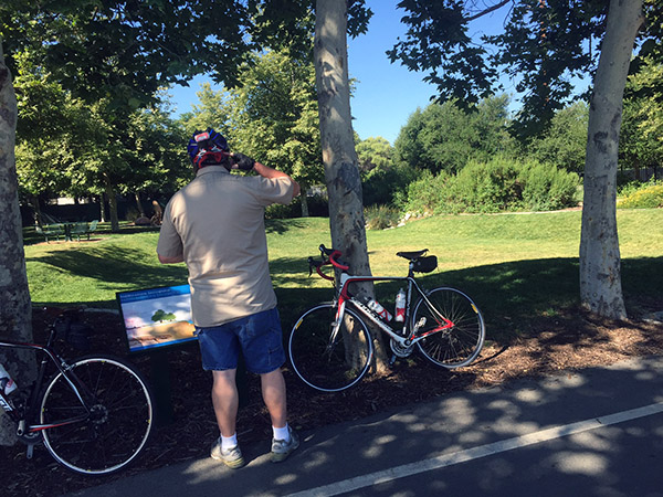 Mark reads a sign by a park with bikes in view