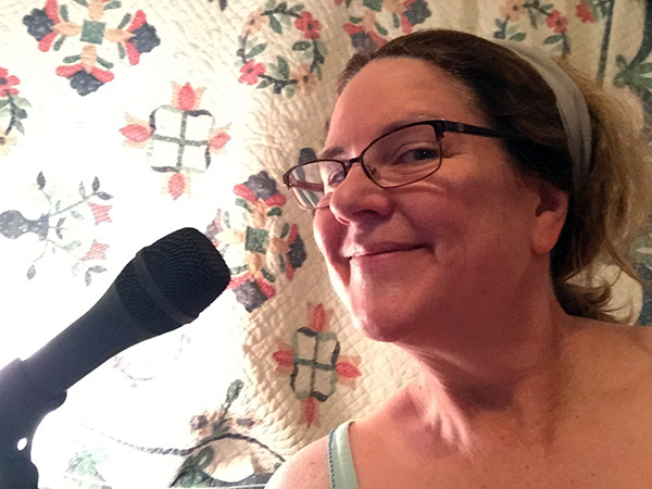Laurie wearing her P.J.s by the mic in front of a quilt hung over the window