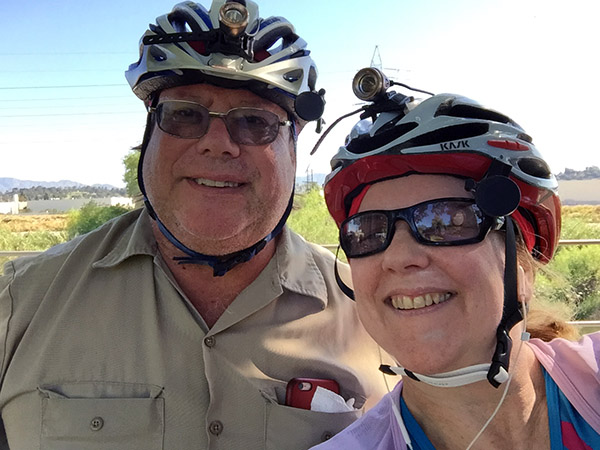 Laurie and Mark wearing bike helmets smile