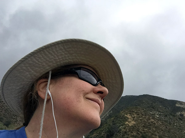 Shot looking at the mountain and sky from below Laurie's chin. She's wearing sun glasses and her hiking hat.
