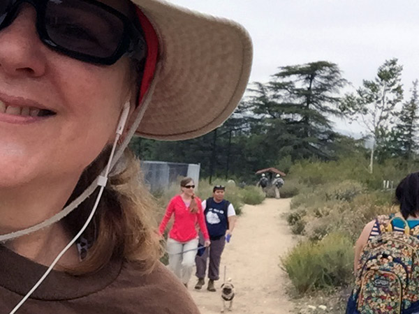 Laurie's face in foreground with Jessie and Nicole and puppies behind her on the hiking trail