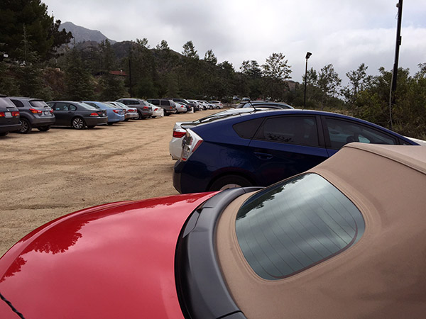 Car park in the mountains with Laurie's red convertible in the foreground