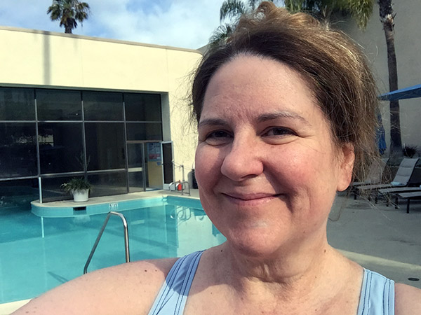 Laurie in front of an outdoor swimming pool with an opening in large block windows to the pool within