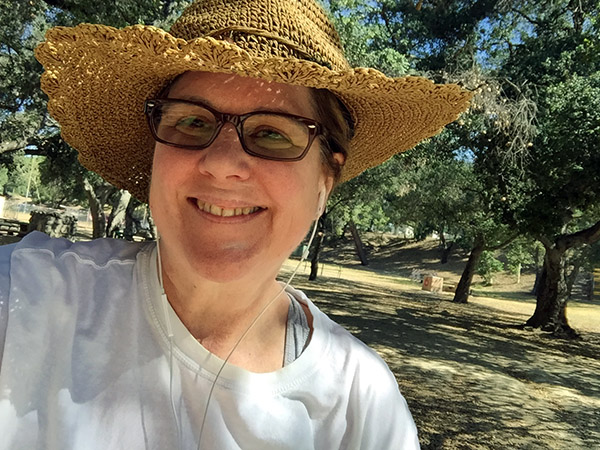 Laurie in her fancy woven sunhat smiles under trees in the park.