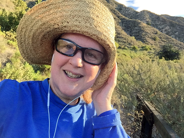 Laurie on the trail holding her straw hat brim down with one hand