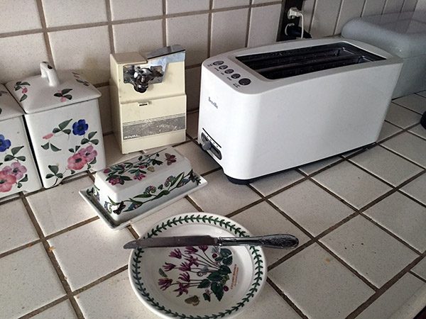 Toaster and botanical garden plates on a white tiled counter