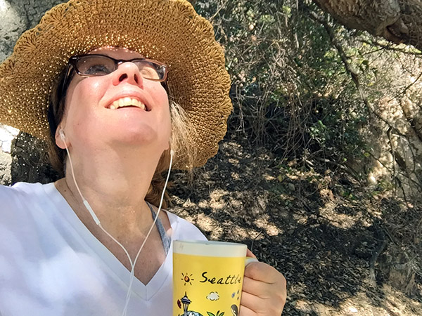 Laurie in a straw hat looking up outside on a sunny day holding a mug of coffee that says Seattle on its side