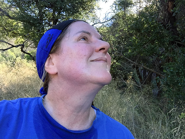 Laurie gazing up in blue headscarf, smiling on the trail