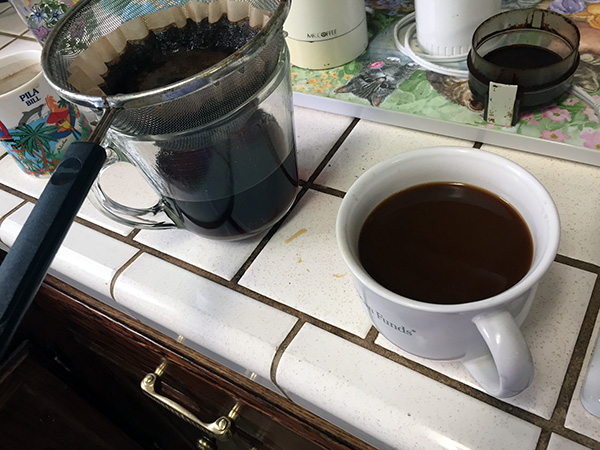Coffee grounds in a strainer over a glass measuring cup on the counter next to a cup of coffee.