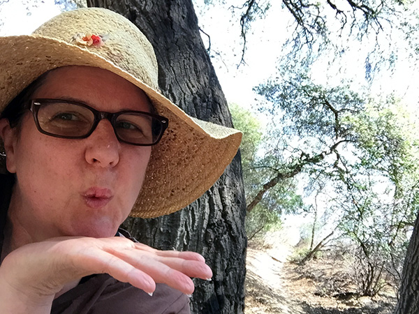 Laurie blows a kiss near an oak tree