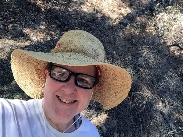 Laurie in sunhat and sunglasses in the shadow of a tree