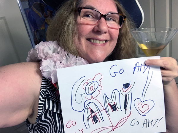 Laurie dressed up holding a sign that says Go Amy!